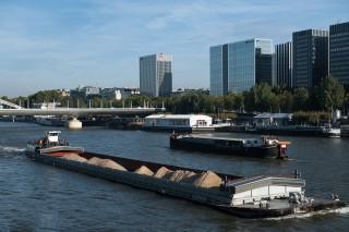 Des péniches et des barges se croisent sur la Seine à Paris.